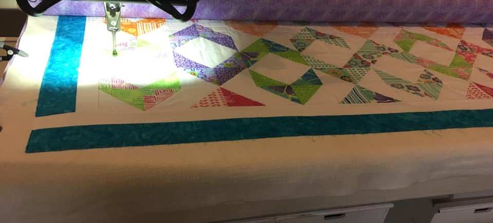 colorful rainbow half triangle quilt top on long arm machine